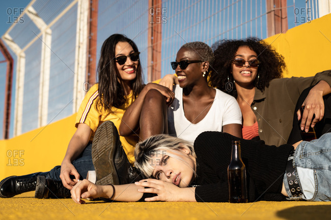 Cheerful young diverse female friends celebrating meeting in city