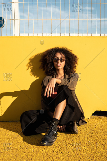 Thoughtful youthful black female hipster in sunglasses and with Afro hairstyle looking at camera and sitting in sunlight on yellow asphalt on stadium