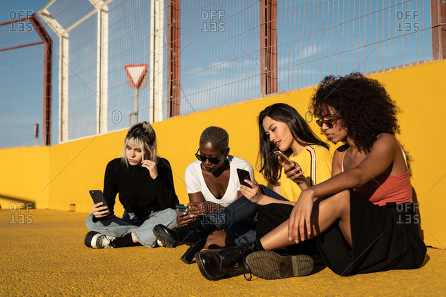 Carefree young multiracial female friends using smartphone in stadium