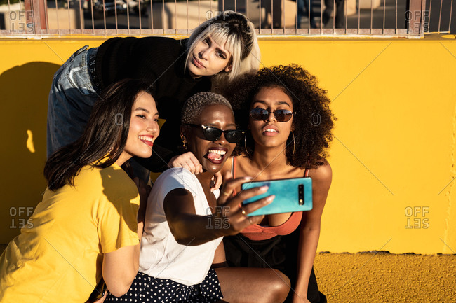 Cheerful young diverse female friends taking selfie on smartphone in street