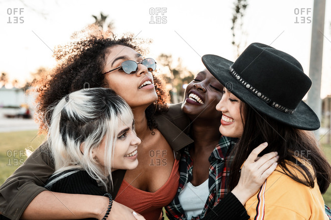 Group portrait of diverse young women wearing clothes in hipster style looking at each other with smiles and hugging together
