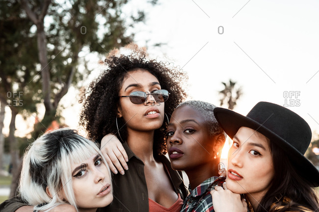 Multiethnic group of female hipsters cuddling with each one