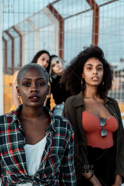 Diverse group of female friends wearing clothes in hipster style looking at camera seriously standing in urban area next to metal fence