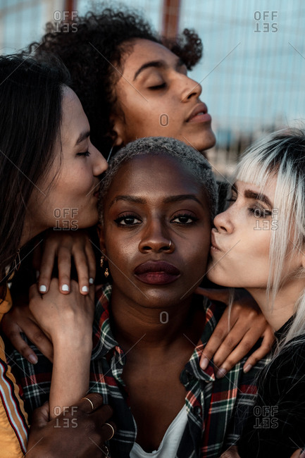 Portrait of young black short haired woman looking at camera with serious face while female friends supporting with hugs and kisses