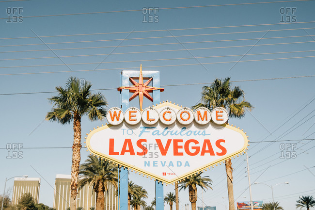 Las Vegas, Nevada, USA - December 7, 2017: Green exotic palm trees and signpost Welcome to fabulous Las Vegas Nevada on road on bright day