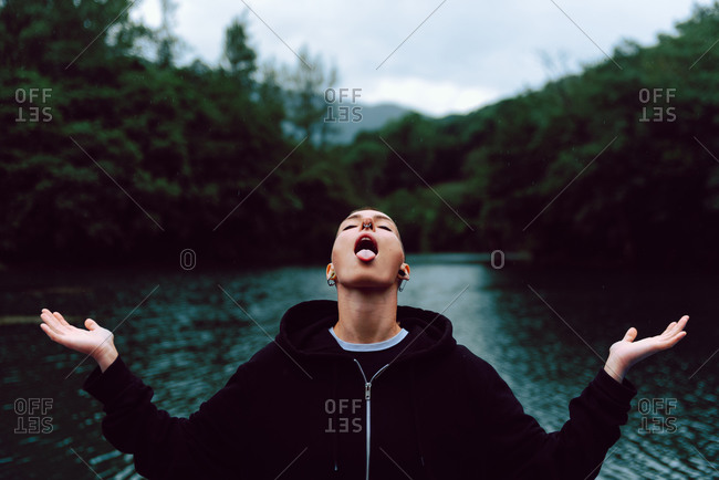 Short haired female with piercing wearing black hoodie and spreading hands while catching raindrops with tongue near green forest and pond
