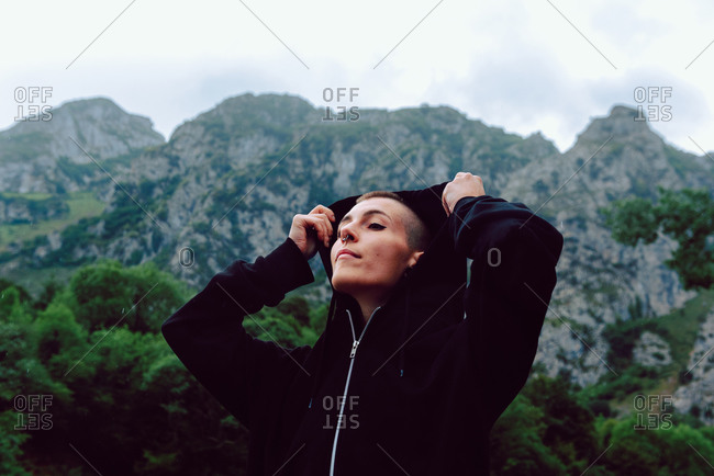 Young extraordinary woman with short hairstyle and piercing in casual clothing looking up to sky with pond among green plants on blurred background