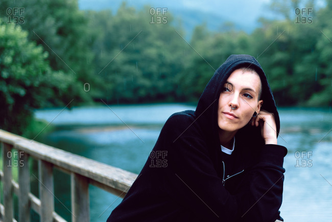 Pensive female millennial with short hairstyle in black hoodie leaning on wooden fence of bridge and looking away with turquoise pond and green plants on blurred background