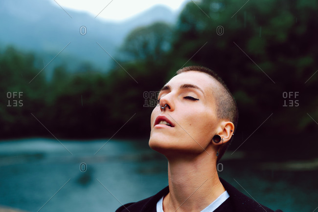Young extraordinary woman with short hairstyle and piercing in casual clothing facing head up with closed eyes to sky with pond among green plants on blurred background