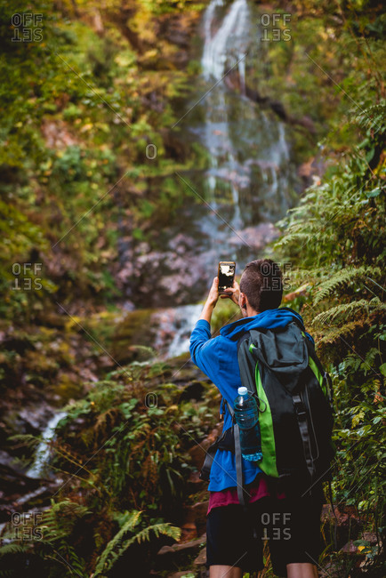 Back view of anonymous woman with professional camera and backpack looking away while standing at waterfall in forest in summer day