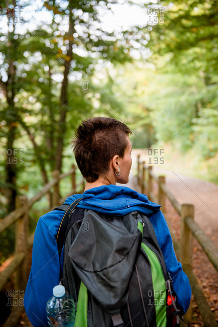 From above back view of unrecognizable tourist standing on wooden bridge and looking at natural landscape in forest