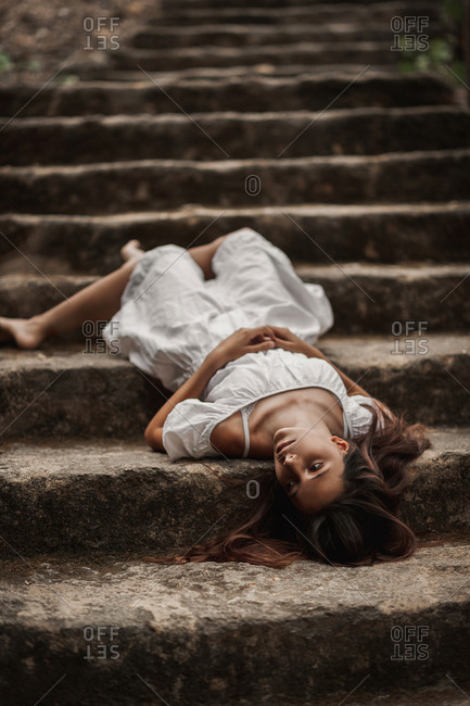 From above of tender charming young female in white dress lying down vulnerably on stairs in autumnal park looking away