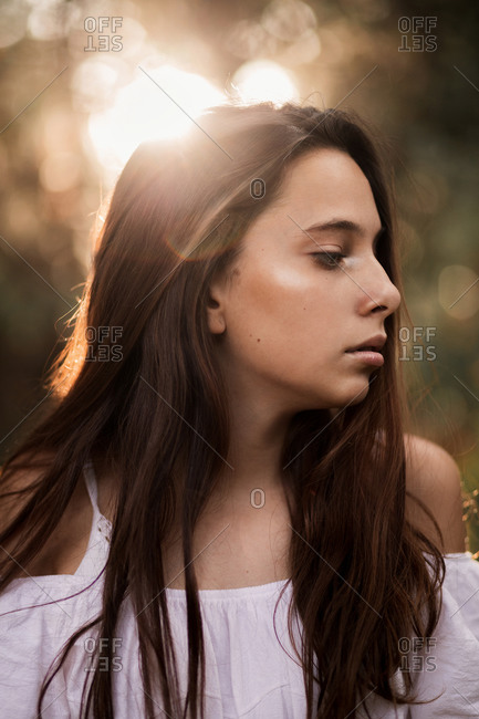 Side view of tender gorgeous young woman in white dress embracing shoulders standing in calm park and looking away