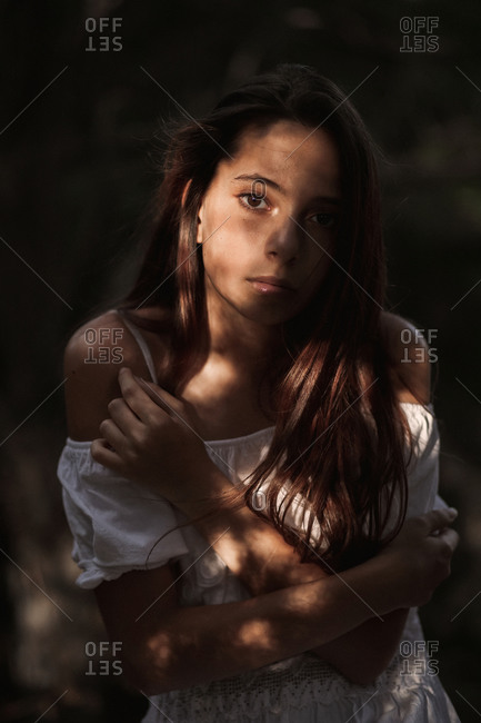 Side view of tender gorgeous young woman in white dress embracing shoulders standing in calm park and looking at camera