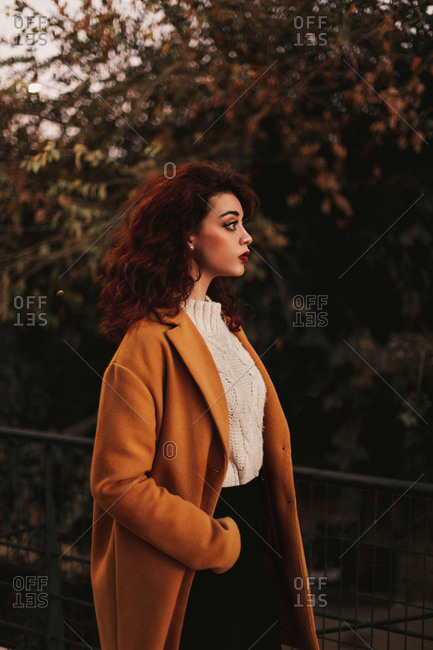 Side view of young sensual female with dark curly hair wearing knitted jumper and overcoat standing in park putting hand on metal railing while looking away with thoughtful look
