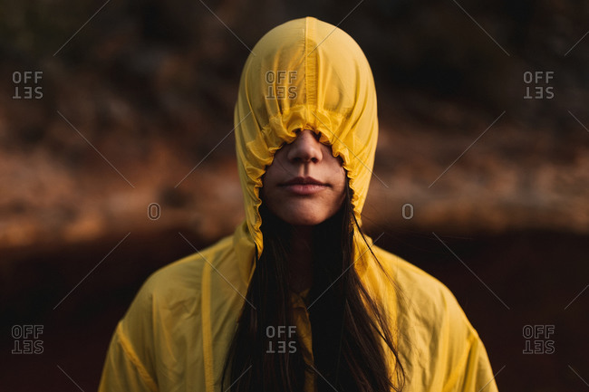 Young lady in yellow raincoat strolling in nature