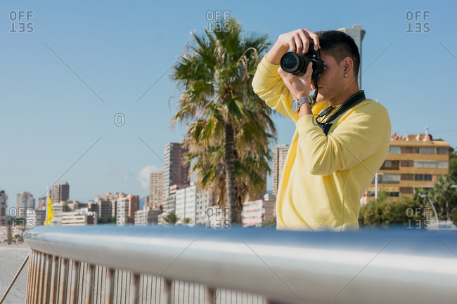 Inspired young male photographer in yellow casual sweatshirt talking photo on camera standing on city quay in sunlight