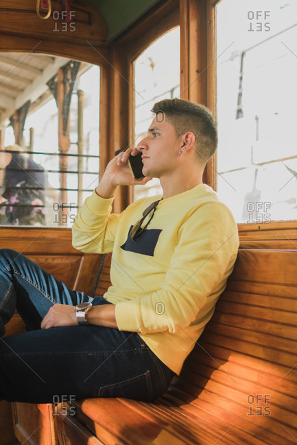Side view of young male in casual clothing speaking on mobile phone while sitting on wooden bench in old train
