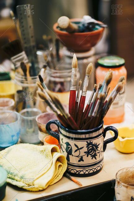 From above of table with cans with colors and paint brushes located around white ceramic cup with blue patterns and brushes inside