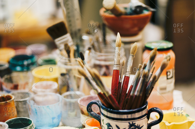 Paintbrushes in ceramic cup with pattern located on table among art tools