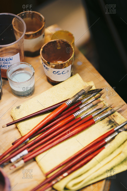 Paintbrushes on table among art tools