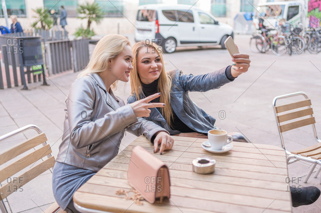 From above of content stylish ladies in casual clothing taking selfie on mobile phone while drinking coffee on outdoors terrace of cafe