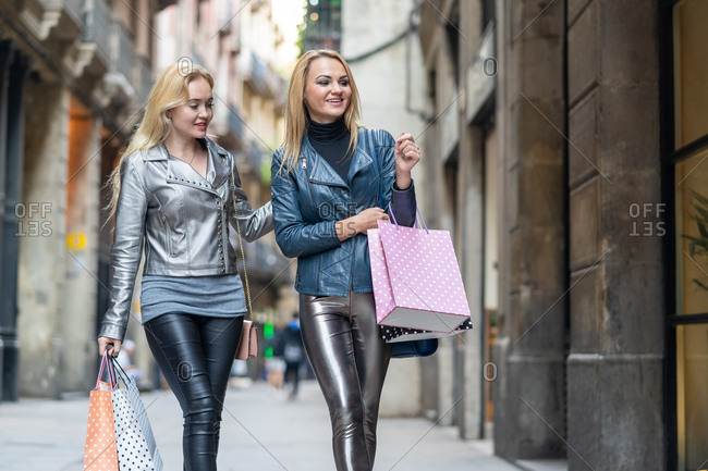 From below of blond haired female friends in trendy clothes walking with shopping bags on town street