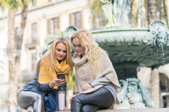 Low angle of blond haired women in casual warm wear sitting with crossed legs near fountain and sharing mobile phone
