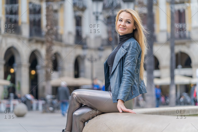 Side view of gorgeous blonde in shiny stylish pants and jacket sitting with crossed legs on fence of fountain smiling away in old city
