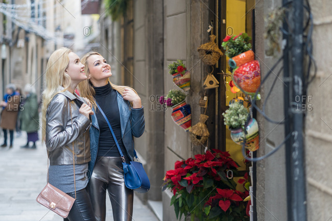 Side view of young blond haired ladies in stylish casual outfits checking shop window during walk at city street