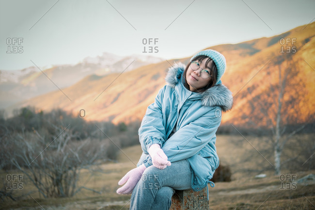 Asian woman sitting resting in nature contemplating beautiful mountain landscape during hiking
