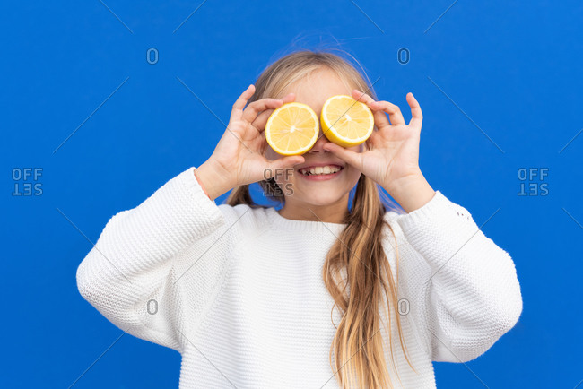 Overjoyed blond haired girl in white sweater smiling while covering eyes with bright lemon slices isolated on blue background