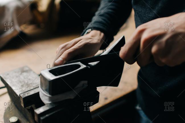 Crop craftsman checking axe in workshop