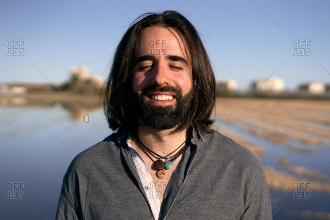 Man standing in front of lake on shore among short yellow lakeside grass with closed eyes and a smile