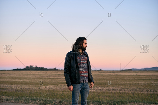 Man with long hair and beard standing in middle of field at dusk and looking away with concern