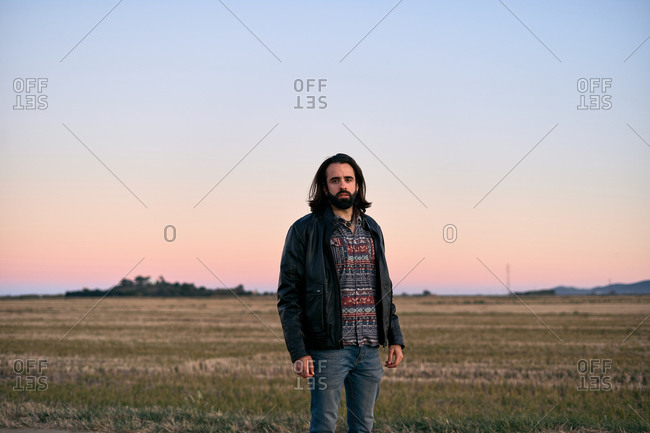 Man with long hair and beard standing in middle of field at dusk and looking at camera with concern
