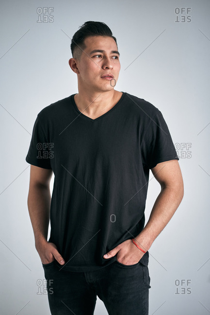 Serious youthful ethnic man in casual clothes looking away and putting hands in pockets on gray background in studio