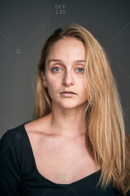 Serious woman with blue eyes and light long hair looking at camera on gray background in studio