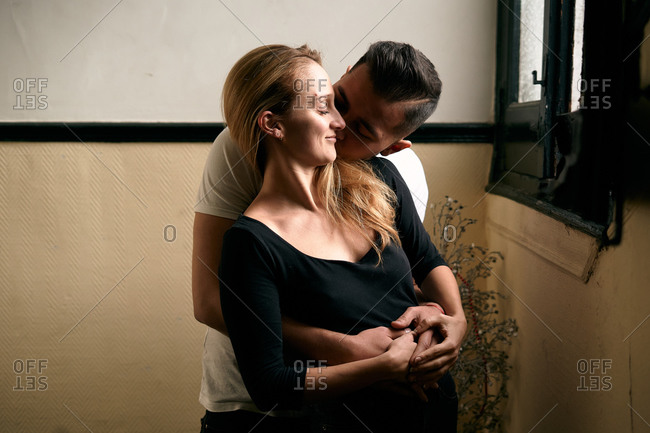 Romantic couple hugging in room at home