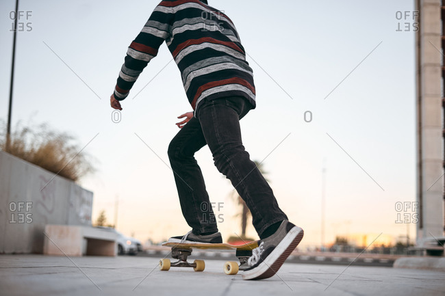 Cropped unrecognizable active male skateboarder wearing hat and striped sweater with jeans skating on city street