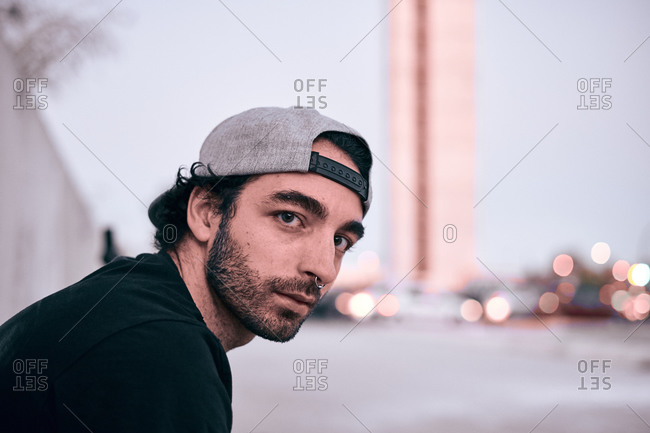 Side view of serious hipster bearded guy with nose piercing wearing black t shirt and grey cap sitting in city street and looking at camera