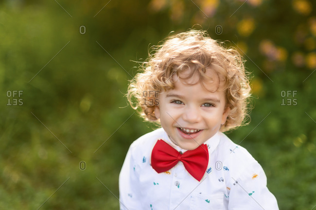 From above of joyful curly haired little boy in shirt and bow tie laughing and looking at camera with green grass on blurred background