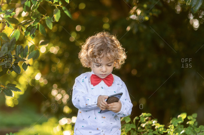 Little curly haired boy in shirt and red bow tie using mobile phone with green plants on blurred background