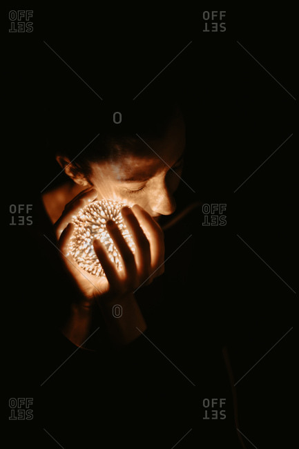 High angle of naked lady covering chest with hand and holding luminous ball in dark