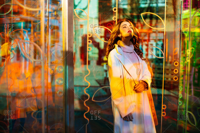 Gorgeous lady with red lipstick in trendy coat and sweater standing with closed eyes among colorful neon signs at city street