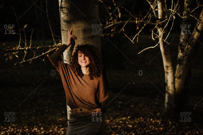 Pleased curly haired lady in casual wear touching autumn yellow leaf and smiling in woods