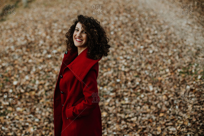 From above of curly haired woman smiling and looking at camera with golden fallen leaves on blurred background