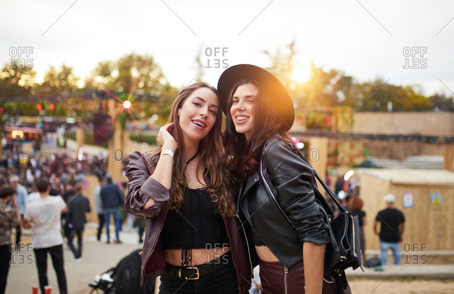 Long haired fashion friends in leather jacket and hat dancing raising hands with two fingers up and looking at camera on festival in sunny day