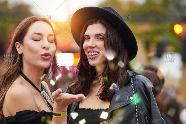 Charming long haired stylish girl friends confidently looking at camera in bright day at festival