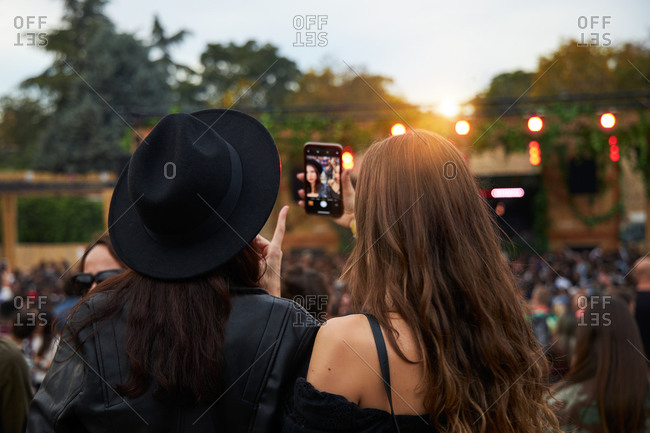 Back view of stylish girl friends in black hat taking selfie and watching photo on mobile phone in bright day at festival